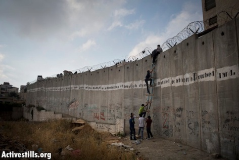 Palestinians use a ladder to climb over the Israeli separation wall in A-Ram, north of Jerusalem, on their way to Al-Aqsa mosque in the Old city of Jerusalem to attend the second Friday prayer in the fasting month of Ramadan, 19 July 2013. (Photo: Oren Ziv/Activestills.org)