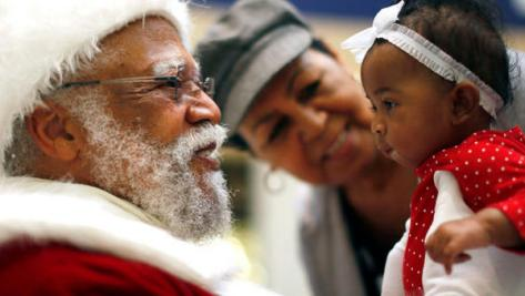 African American Santa Claus Langston Patterson (L), 77, greets four-month-old Raelyn Price as her grandmother Gloria Boissiere looks on, at Baldwin Hills Crenshaw Plaza mall in Los Angeles, California, December 16, 2013. Patterson has worked as Santa since 2004 at the mall, which is one of the few in the country with a black Santa Claus. (REUTERS/Lucy Nicholson)